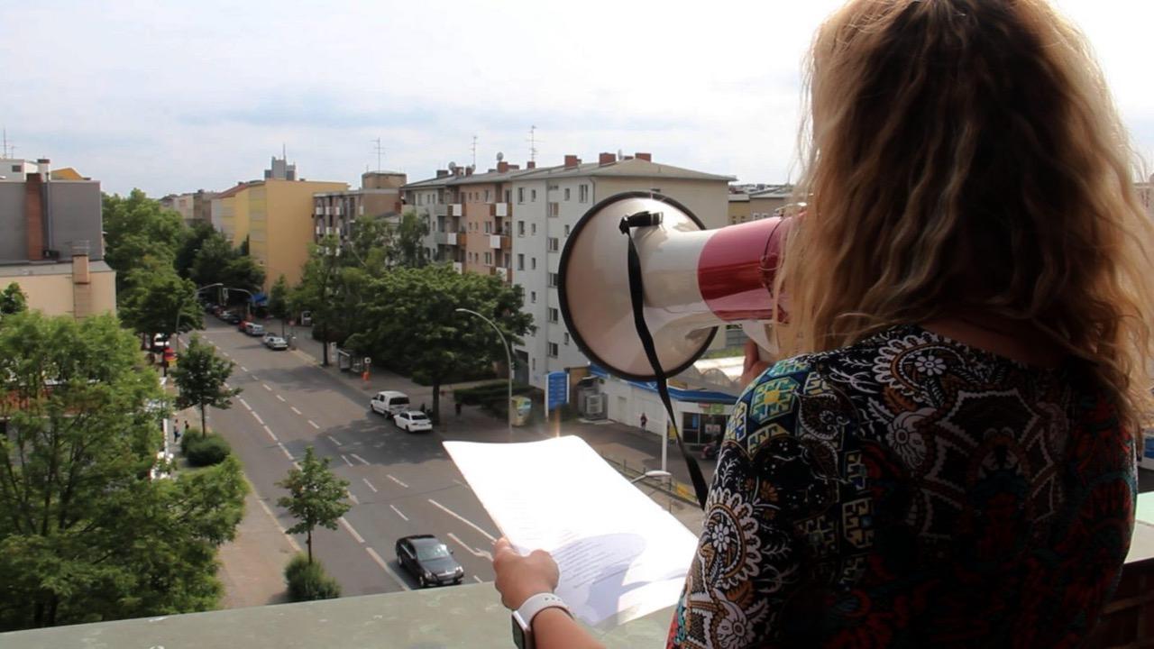 Sängerin mit Megaphon singt vom Kirchturm herunter